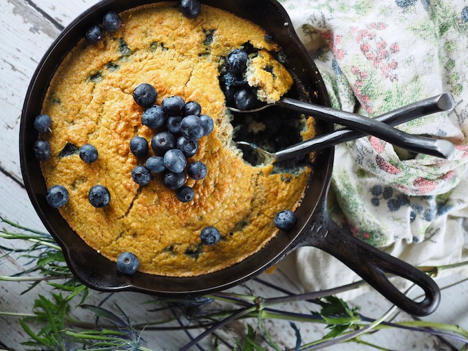 overhead view of Coconut Flour Blueberry Skillet Bread with two spoons and tea towel