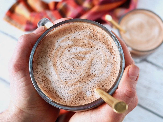 two hands holding a glass mug of Creamy Dairy-Free Hot Cocoa with gold spoon