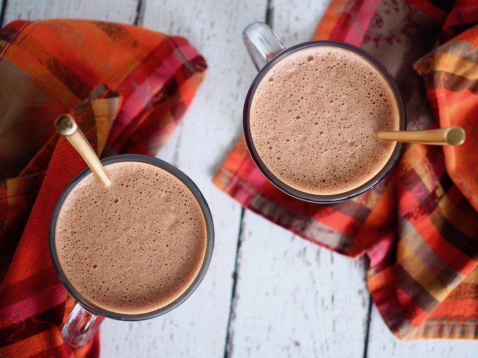 overhead view of two mugs of Creamy Dairy-Free Hot Cocoa on white wooden table with plaid napkins