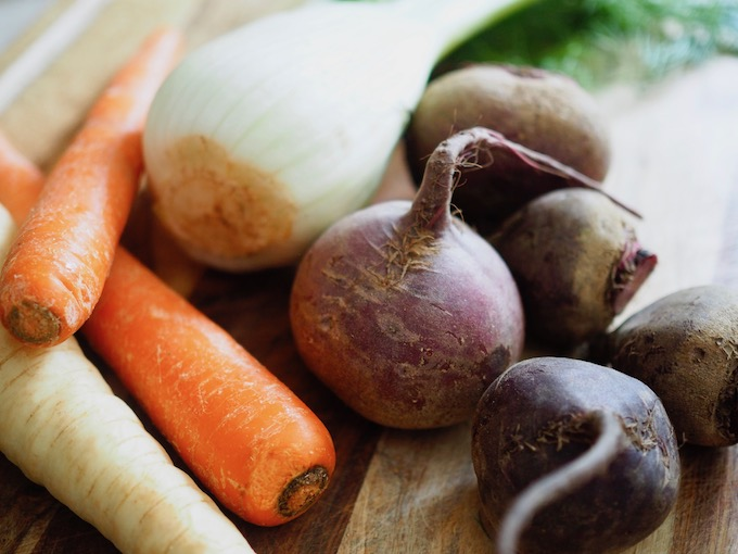 carrots beets parsnips and fennel on wood cutting board