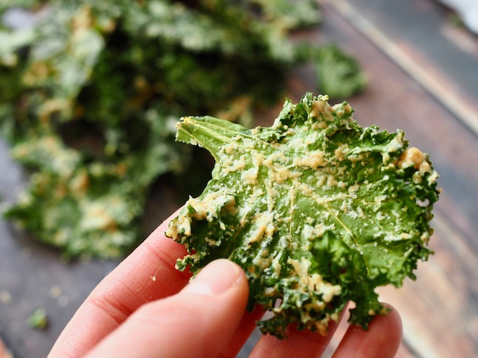closeup of a hand holding a single baked Easy Tahini Garlic Kale Chip