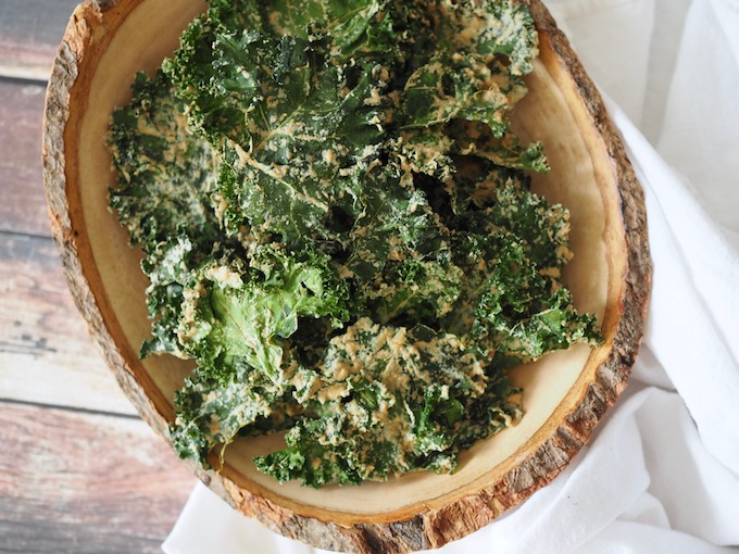 overhead view of wooden bowl of kale chips on wood table with white fabric napkin