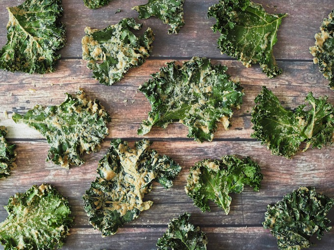 kale chips spread over a wooden tabletop