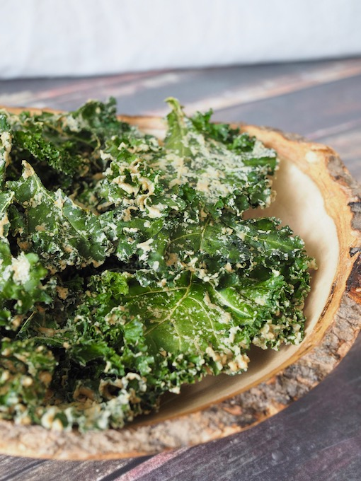 wooden bowl of Easy Tahini Garlic Kale Chips on wooden table with white backdrop