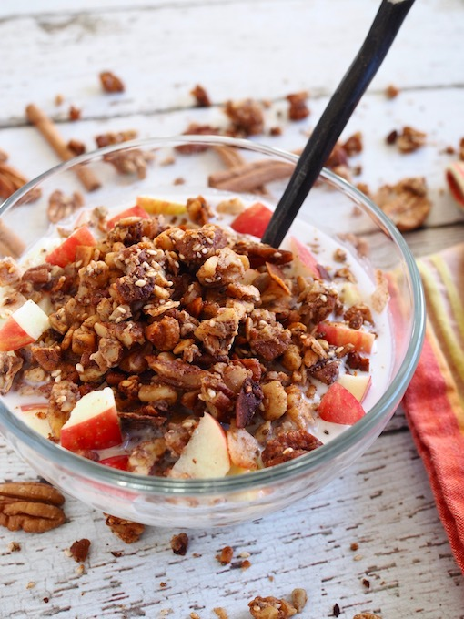 bowl of cinnamon crunch grain-free granola on white wood table with apples and pecans