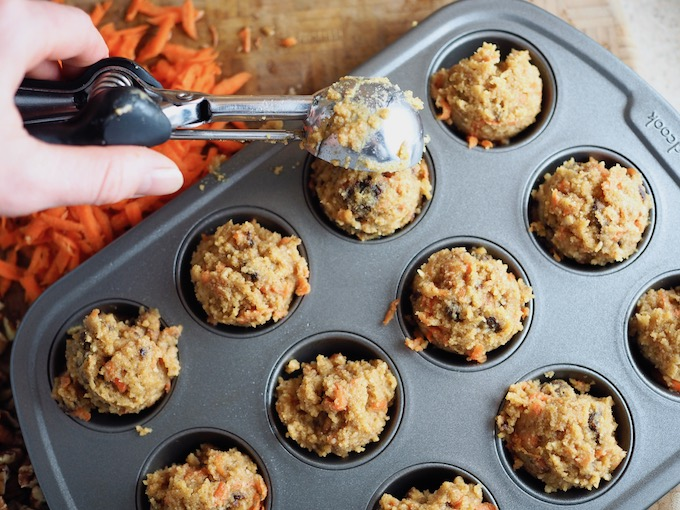 scooping cupcake batter into a mini-muffin tin