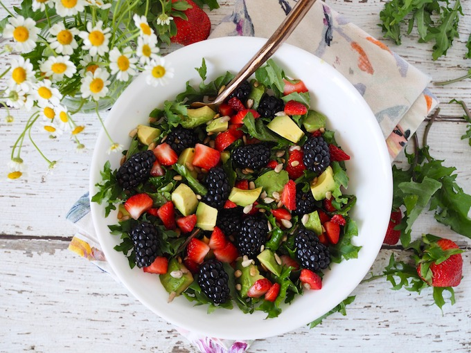 salad with berries avocado and sunflower seeds on white wood table with fresh flowers