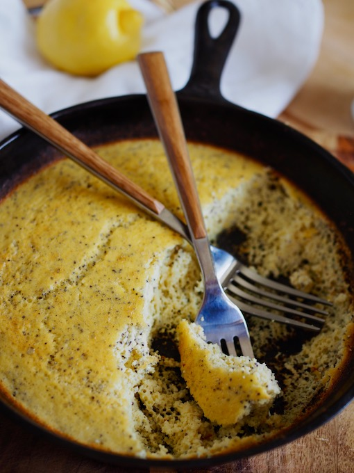 two forks digging into cast iron skillet of lemon poppy seed coconut flour bread on wood table