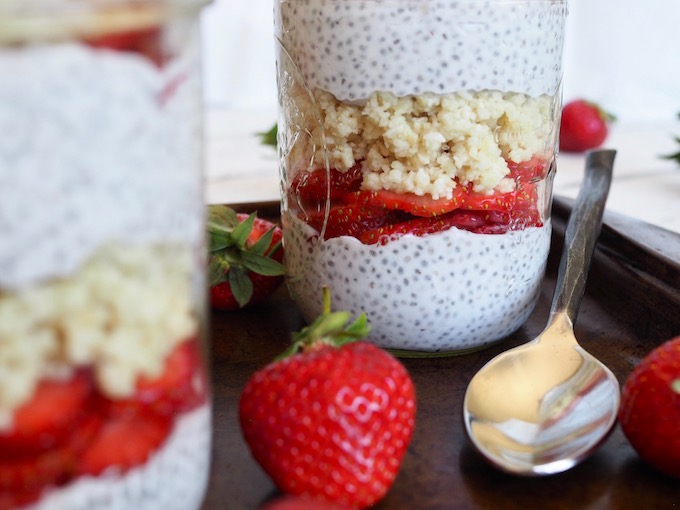 close up side view of two mason jars layered with chia pudding fresh strawberries and macadamia coconut shortbread crumble