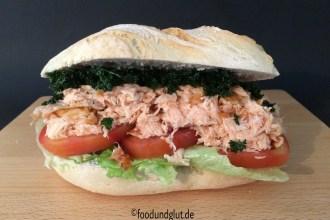 Brötchen, belegt mit gezupften und heiß geräuchertem Lachs, ergibt Pulled Salmon Burger. Belegt mit Tomate, Eisbergsalat und frittierter Petersilie