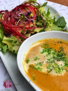vorspeise mit suppe und salat auf dem teller