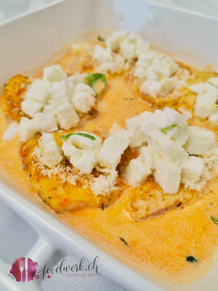 Hähnchen al forno bestreut mit Mozzarella und Sbrinz, bevor es in den Ofen kommt.