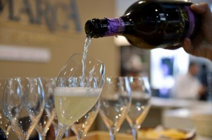 A person poors a glass of Prosecco on April 10, 2016 during the 50th edition of the Vinitaly wine exhibition in Verona. Vinitaly is the world's largest wine event, hosting more than 4164 exhibitors, looking to promote a vast range of rich and exotic varieties of wines, spirits and other alcoholic beverages. / AFP PHOTO / VINCENZO PINTO