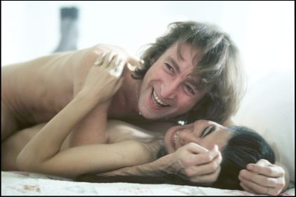 """John Lennon and Yoko Ono during the filming of a video to promote their new album, """"Double Fantasy"""", New York City, November 26, 1980. Filming began in Central Park, then moved to a gallery on SoHo for scenes where they would arrive in a white bedroom, first in street clothes and later in kimonos, strip, and make love. photo credit: ©Allan Tannenbaum"""