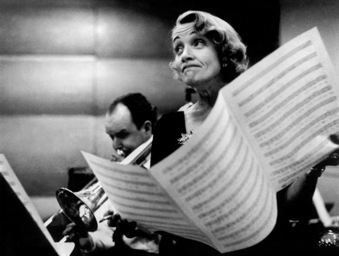 USA. New York City. Marlene DIETRICH at the recording studios of COLUMBIA RECORDS, who were releasing most of her songs she had performed for the troops during World War II, including LILI MARLENE, Miss Otis Regrets.She was 51 years old and starting a come-back in show business.It was a wet and cold November night and work could only begin at midnight, at the advise of Marlene's astrologer. November 1952. (C) Eve Arnold / Magnum Photos No Photograph or digital file may be reproduced, cropped or modified (digitally or otherwise), and its caption may not be altered without prior written agreement from the photographer or a Magnum representative.