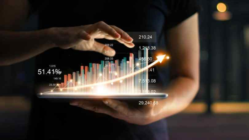 Businessman holding tablet and showing a growing virtual hologram of statistics, graph and chart with arrow up on dark background. Stock market. Business growth, planning and strategy concept
