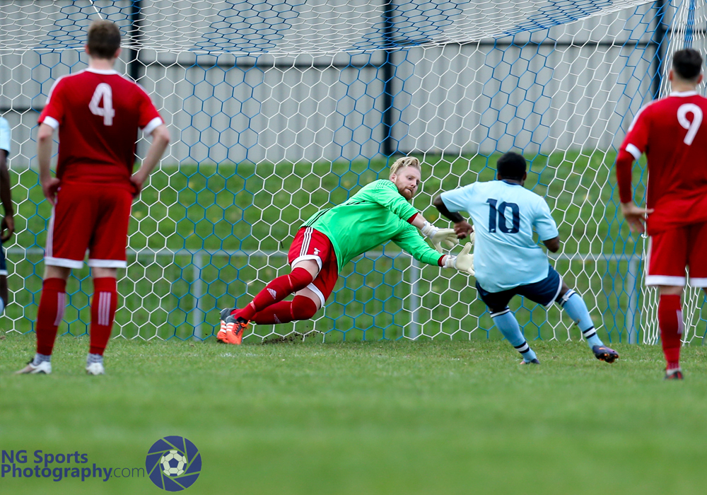 Callum Whitty makes a penalty save for Bracknell Town FC. Photo: Neil Graham.