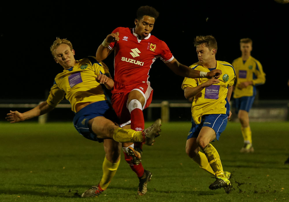 A defensive challenge for Ascot United against MK Dons. Photo: Neil Graham.