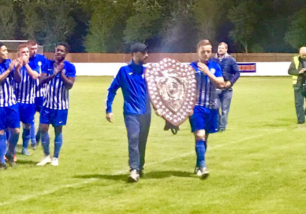 Shane Cooper-Clark with the Hellenic League trophy. Photo: Jochen Cooper.