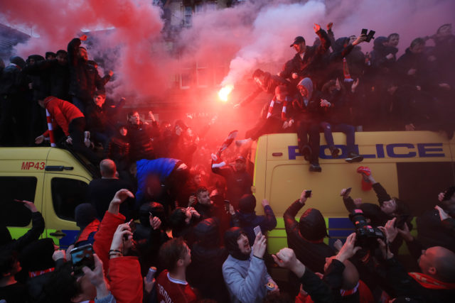 Fans on top of a Police van and flares being let off before the UEFA Champions League, Semi Final First Leg match at Anfield, Liverpool.