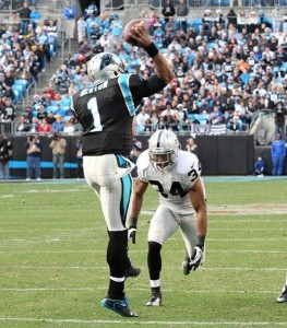 Panthers quarterback Cam Newton throws a pass to evade a blitzing Raiders safety Mike Mitchell. In the fourth quarter, a hit by Mitchell caused Newton to confront referee Jerome Boger, drawing an unsportsmanlike conduct foul.