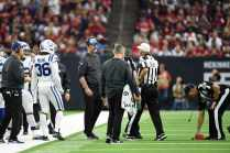 Referee Bill Vinovich responds to a replay challenge while down judge Kevin Codey picks up the challenge flag (Indianapolis Colts).