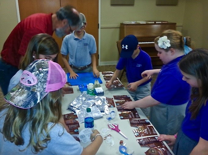 John Cranston, with 4th graders at Whitesburg Christian Academy, assembling recycled coffee bags for the sunshield project
