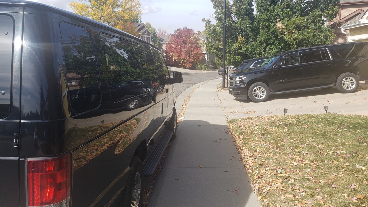 black airport shuttle and black SUV waiting for a ride