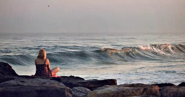 A young woman by the seashore staring towards the horizon