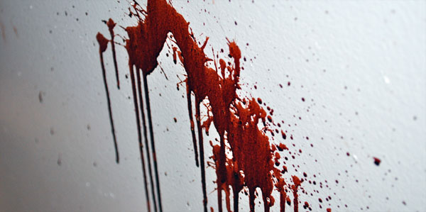 A wall surface with a small splash of fake blood dripping downward