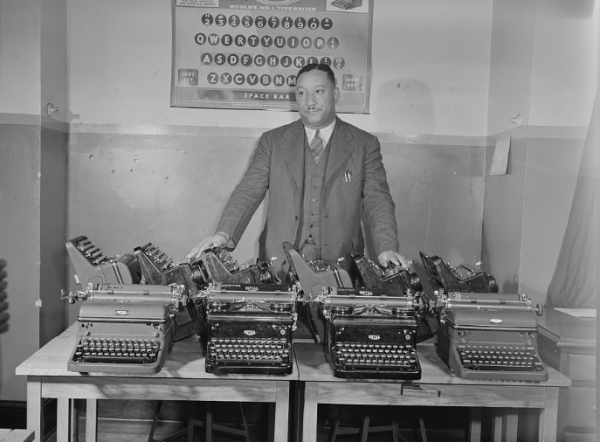"""This photo was taken in 1942 for the Office of War Information. The caption: """"Cortez W. Peters, world's champion portable typist, is shown with ten late model standard size typewriters which he turned over to the government to aid the drive for 600,000 machines for the Army and Navy. The typewriters were taken from three business schools which Mr. Peters operates in Washington, D.C., Baltimore, Maryland, and Chicago, Illinois."""" (Library of Congress photo)"""