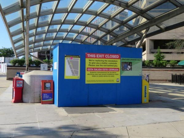"""The Van Ness Metro station's west entrance, blocked off. The sign says: """"We're replacing the escalators to give you a better commute. Please use the exit behind you."""""""