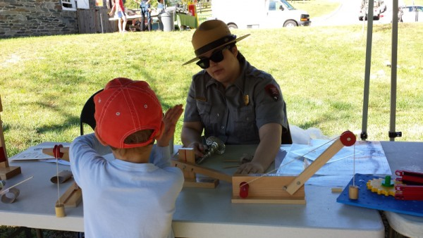 A National Park Service ranger demonstrates simple machines and explains how they relate to the larger equipment in the mill.