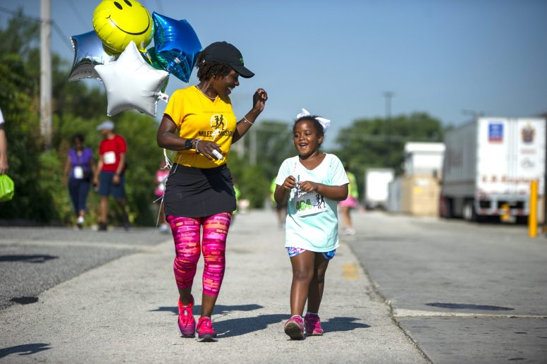 Participants cheer as runners make their way to the finish line on Saturday, Aug. 3, during the annual Miles 4 Missions Run and Walk outside of Living Word Christian Center on Roosevelt Road in Forest Park. | ALEXA ROGALS/Staff Photographer