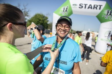 Sheila Frye, right, of Aurora, receives a medal for being a first-time runner for the event on Saturday, Aug. 3, during the annual Miles 4 Missions Run and Walk outside of Living Word Christian Center on Roosevelt Road in Forest Park. | ALEXA ROGALS/Staff Photographer