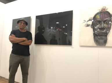 Jesse Howard stands next to one of his pieces, which was inspired by a man he met at Starbucks, during an artists' reception at Robert Morris College's State Street Gallery on Oct. 3.