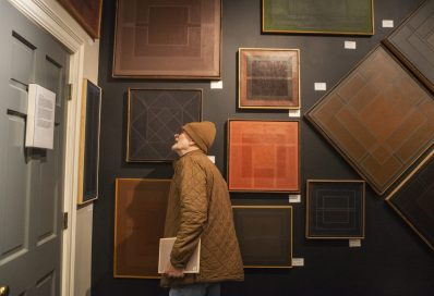 John Chapin, of Oak Park, looks over the artwork hung up before deciding on which piece he wants to buy on Nov. 15, 2019, during the art exhibition for Irving Newman's work at Studio 8 in Forest Park. | ALEX ROGALS/Staff Photographer
