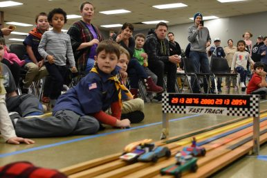 Scouts and parents, including Dylan Kernkamp, watch as cars race down the track. | Photo by Jill Wagner