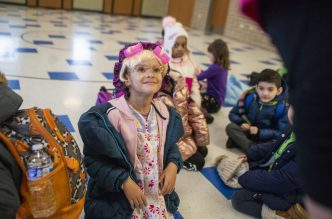 "First grader Bria Moore, talks with faculty members as she wears glasses, a wig and hair rollers to represent ""100 year olds"" on Friday, Jan. 31, 2020, at Betsy Ross Elementary School."