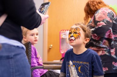 Lincoln Jackson, 5, of Forest Park, gives his best tiger impression as his mom snaps a photo of his face painting during the Leap Day History & Community Festival at Howard Mohr Community Center in Forest Park. | SHANEL ROMAIN/Contributor