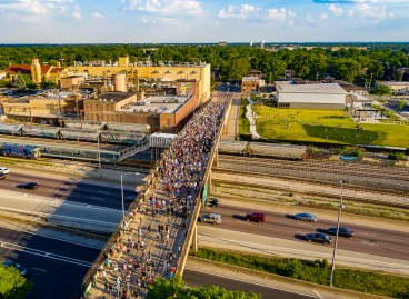 "An overhead photo shows the Circle Avenue bridge in Forest Park with over 1,000 participants for Forest Park Against Racism's ""Meet us at the Bridge"" event. 