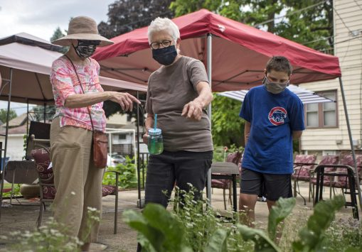 Etta Worthington (center) shows visitors her home vegetable garden, one of the stops in the Historical Society of Forest Park's Garden Walk on July 11. | Alex Rogals, Staff Photographer