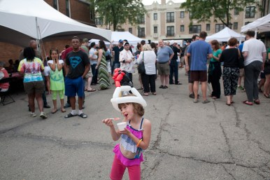 Josie Pfeiffer, 6, enjoys a frozen treat during a block party in Forest Park to benefit Opportunity Knocks.