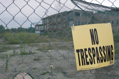 "A ""No Trespassing"" sign on the gate surrounding the demolition site."