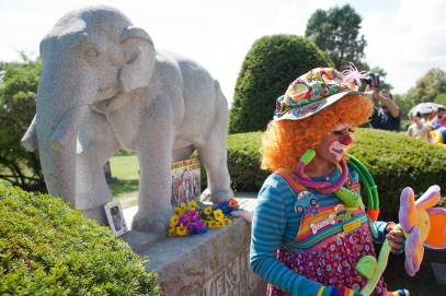 A clown Sunday pauses after placing flowers at Showmen's Rest monument during a memorial ceremony at Woodlawn Cemetery in Forest Park for circus artists who died in a 1918 train accident.