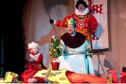 """At the end of """"The Twelve Days of Christmas,"""" the king, played by Jeff Kiel, places his pear tree on an exhausted jester, Justin Martin. (David Pierini/staff photographer)"""