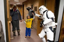 Nehemiah Overton, center, is greeted with a high-five from a Star Wars storm trouper during Mini Comicon at the Forest Park Public Library Saturday. (David Pierini/photographer)