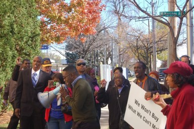 CANDY PROTEST: Protesters shake candy boxes as they gather outside Ferrara Candy Company in Forest Park Oct. 28. They said the company employs almost all temporary workers and that agencies discriminate against African Americans in favor of Latinos. (Photo Michael Romain)