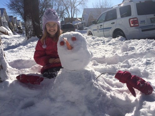 """Cassidy Brown poses with her """"tiny but mighty"""" snowman Monday."""