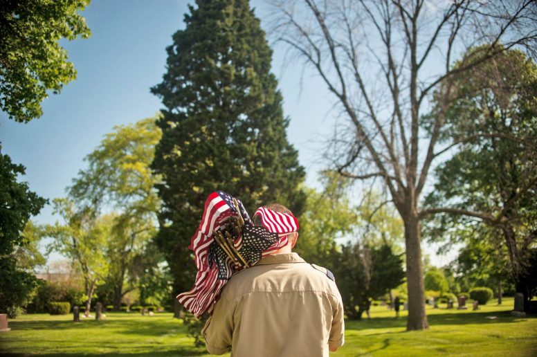 Boy Scout leaders held more than 20 American flags at one time to hand off to the children as soon as they found someone who served in the military buried in Woodlawn Cemetery on Sunday. | William Camargo/Staff Photographer